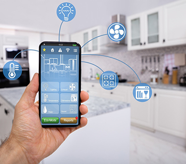 hand holding smart phone, wirelessly connected to kitchen appliances
